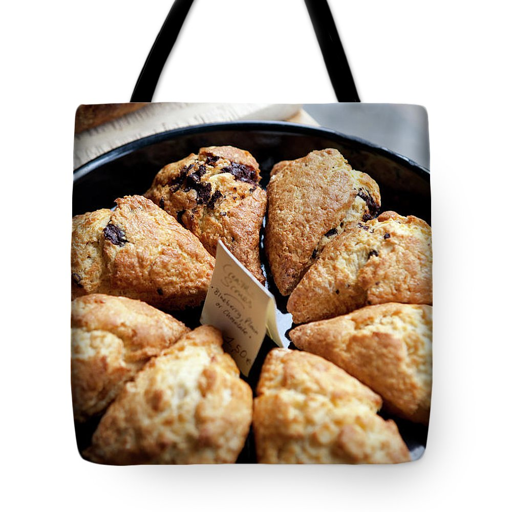 Breakfast Tote Bag featuring the photograph A Variety Of Scones For Sale On Display by Halfdark