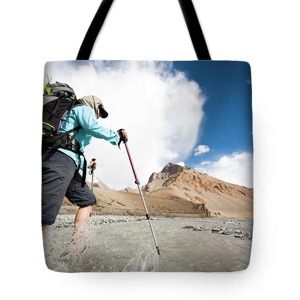 Adventure Tote Bag featuring the photograph A Woman Is Crossing A River, Spiti by Andrew Peacock