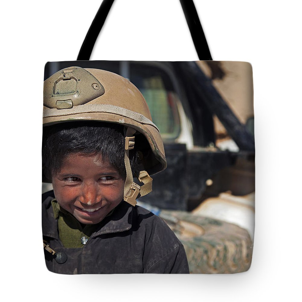 Middle East Tote Bag featuring the photograph A Young Boy Wears A Coalition Force by Stocktrek Images