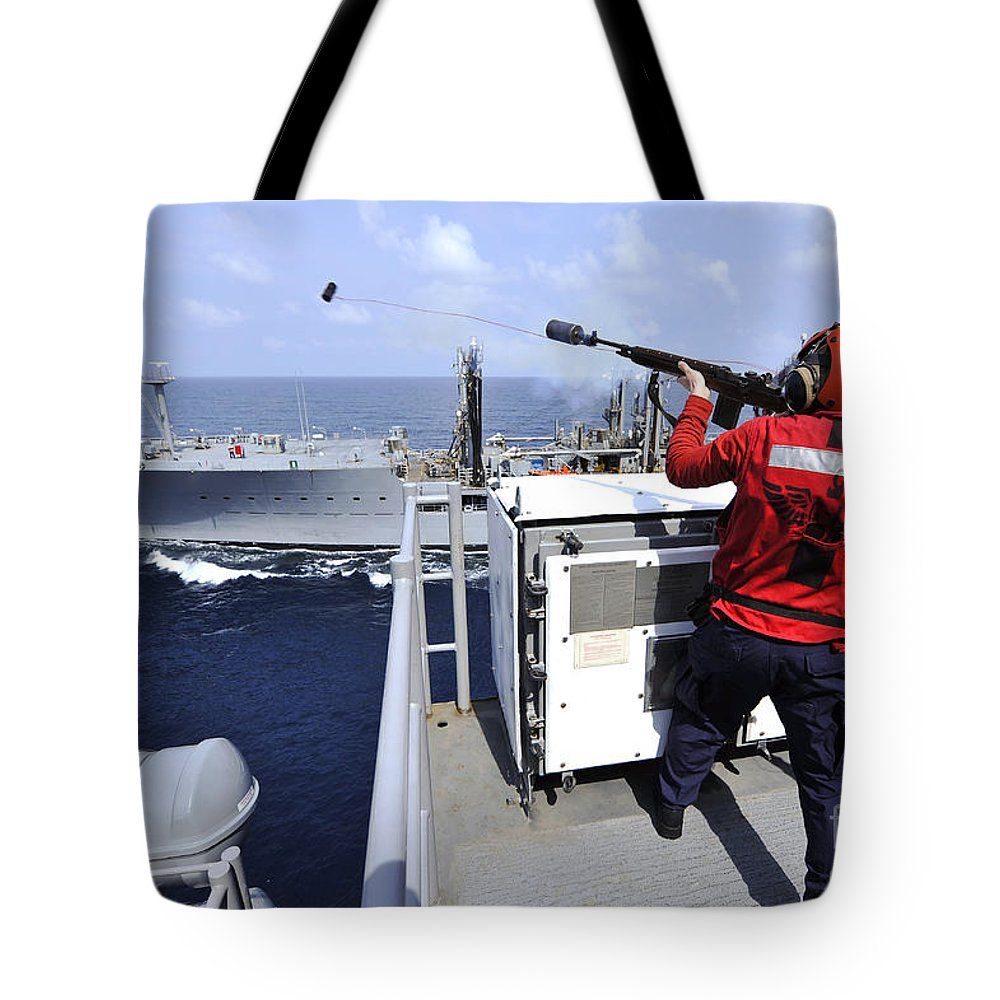 Military Tote Bag featuring the photograph Airman Fires A Shot Line From Uss by Stocktrek Images