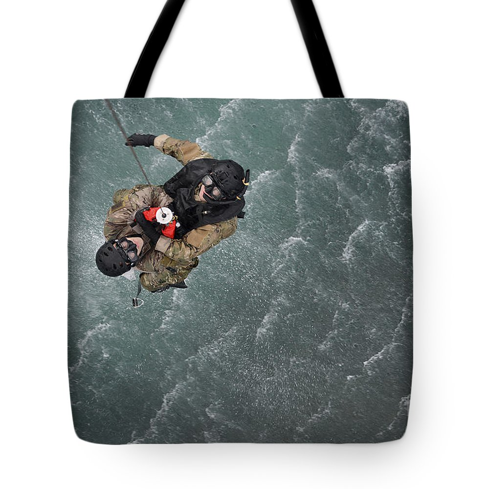 Pararescuemen Tote Bag featuring the photograph Airmen Are Hoisted Out Of The Water by Stocktrek Images
