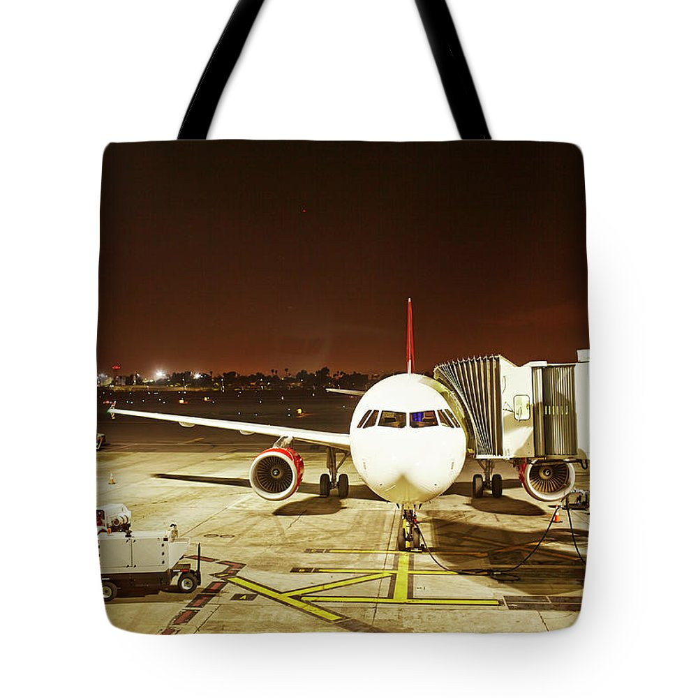 Passenger Boarding Bridge Tote Bag featuring the photograph Airplane Parked At Jetway by Ballyscanlon