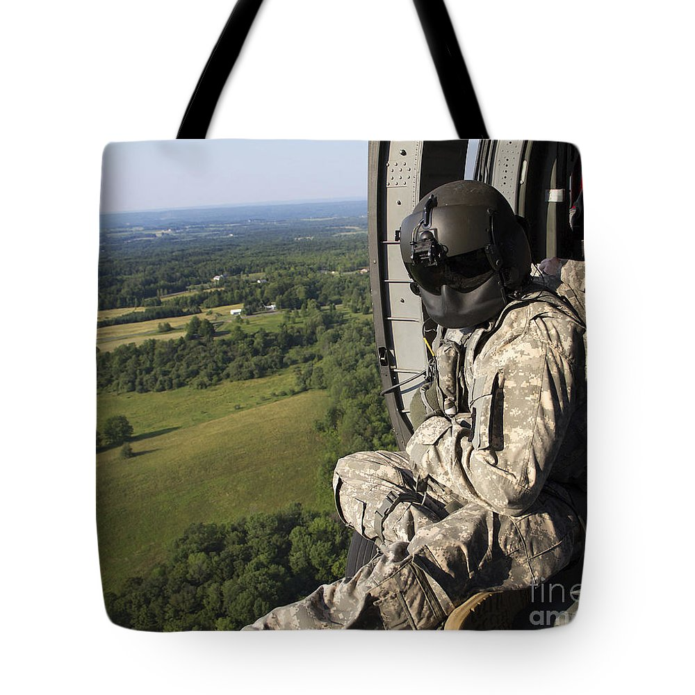 Military Tote Bag featuring the photograph An Army Crew Chief Looks Out The Door by Stocktrek Images