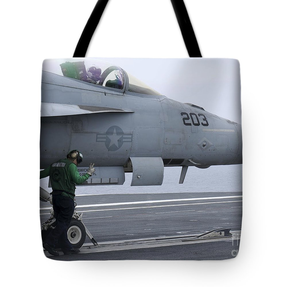 Military Tote Bag featuring the photograph An Aviation Boatswains Mate Prepares An by Stocktrek Images