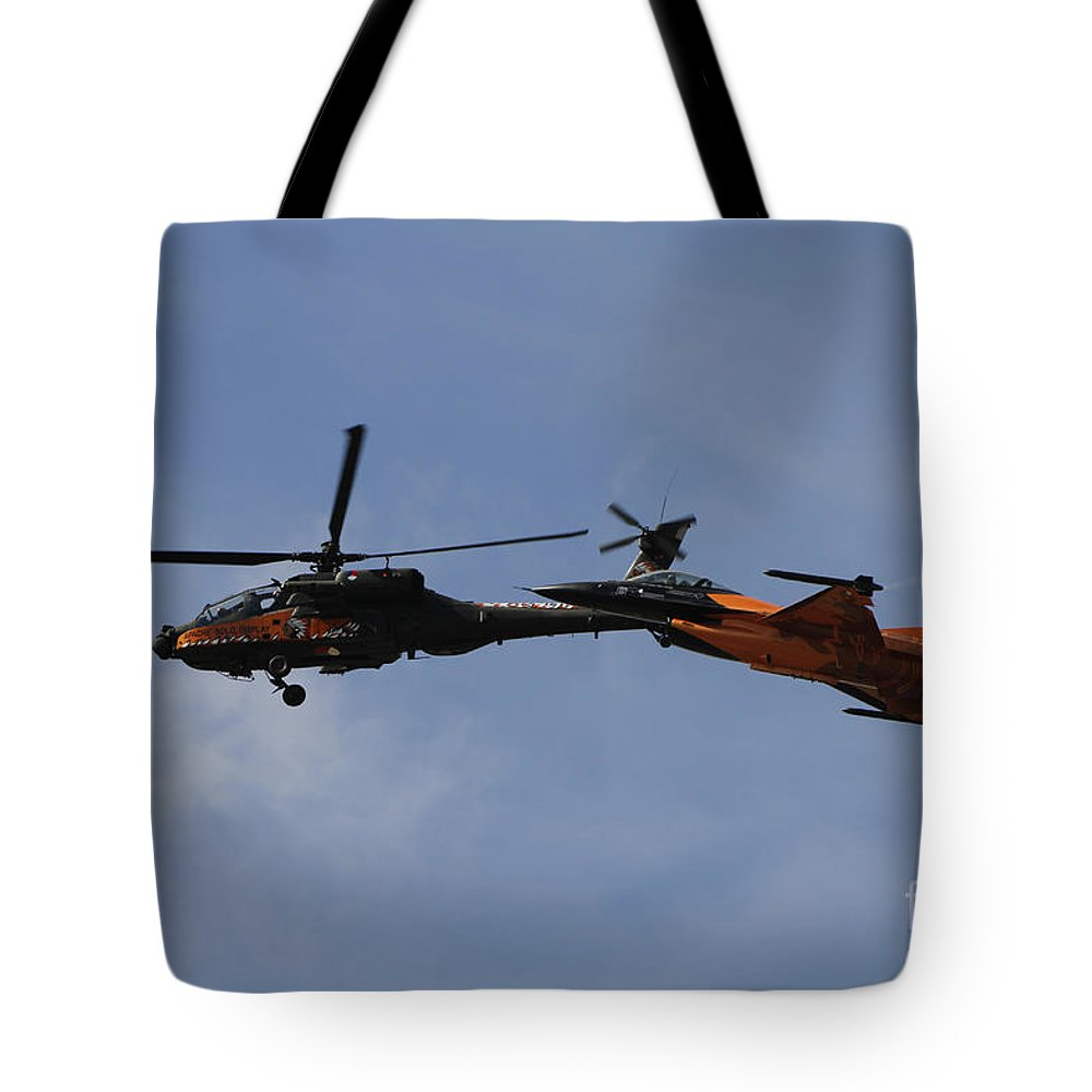 Military Tote Bag featuring the photograph An F-16 Falcon And Ah-64 Apache by Ofer Zidon