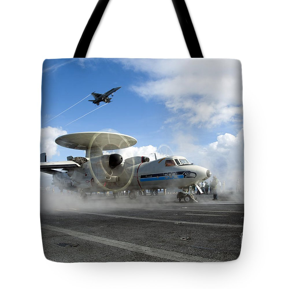 Military Tote Bag featuring the photograph An Fa-18c Hornet Flies Overhead As An by Stocktrek Images