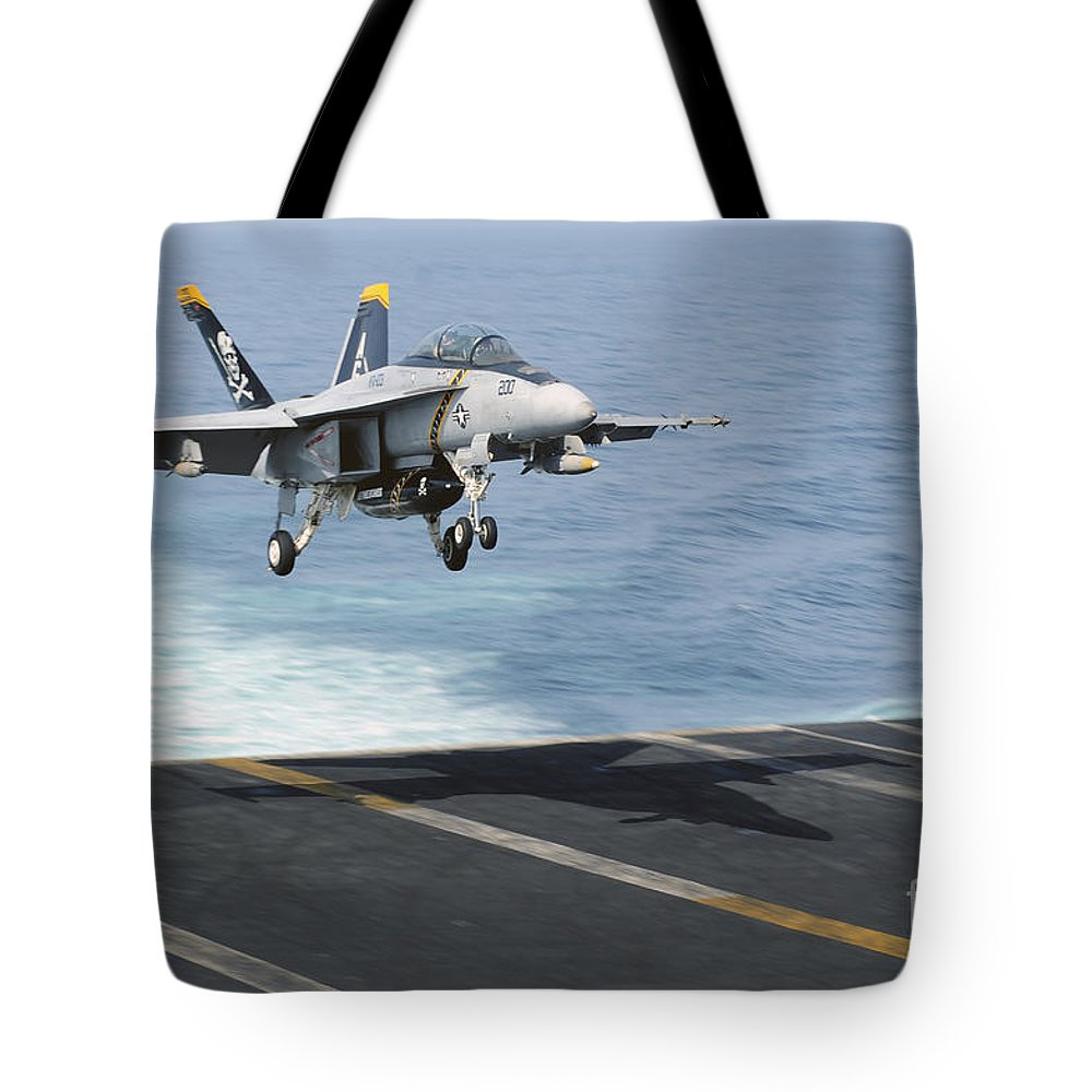 Military Tote Bag featuring the photograph An Fa-18f Super Hornet Prepares To Land by Stocktrek Images