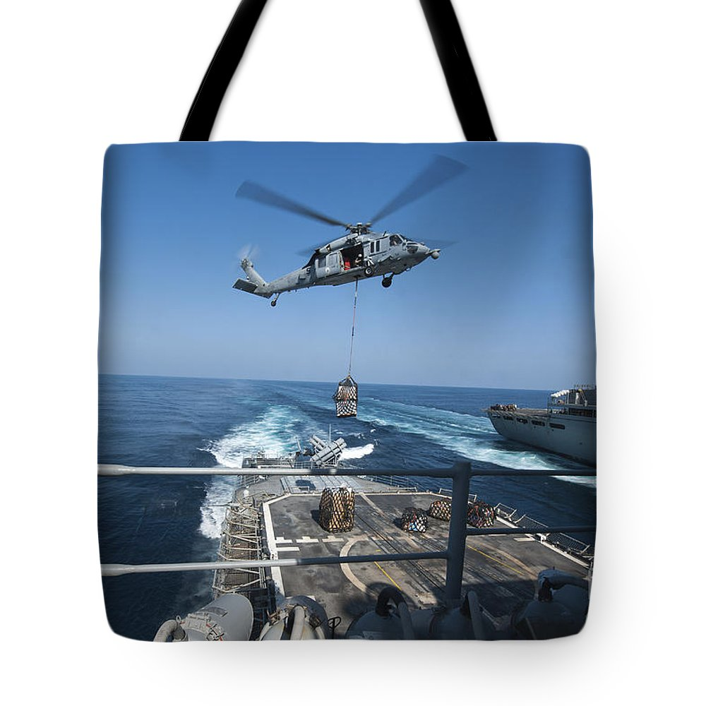 Military Tote Bag featuring the photograph An Mh-60s Sea Hawk Brings Pallets by Stocktrek Images