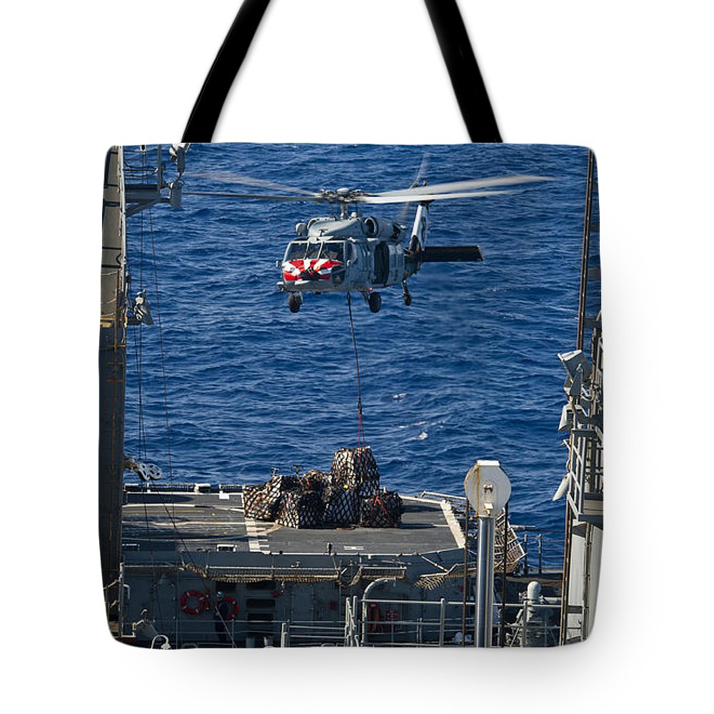 Military Tote Bag featuring the photograph An Mh-60s Sea Hawk Delivers Supplies by Stocktrek Images