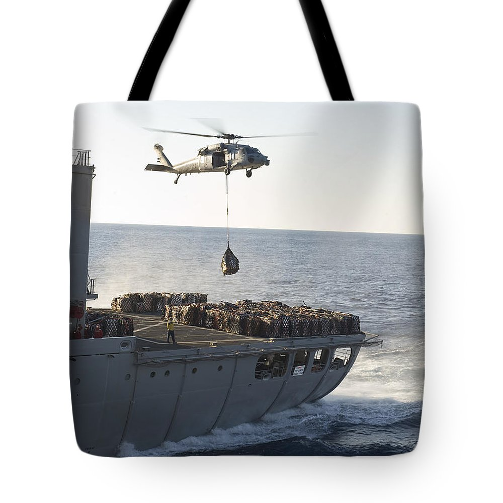 Military Tote Bag featuring the photograph An Mh-60s Sea Hawk Helicopter Carries by Stocktrek Images