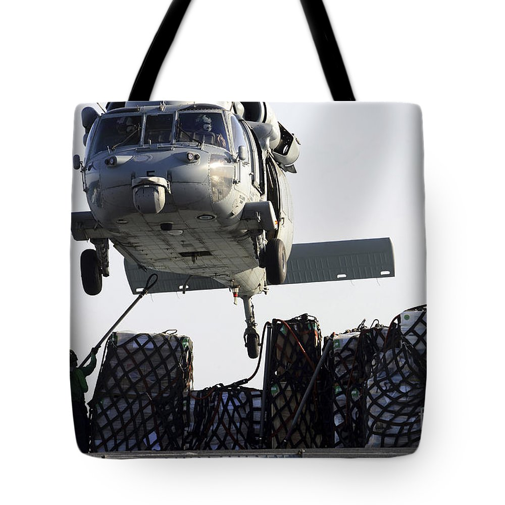 Military Tote Bag featuring the photograph An Mh-60s Sea Hawk Picks Up Supplies by Stocktrek Images