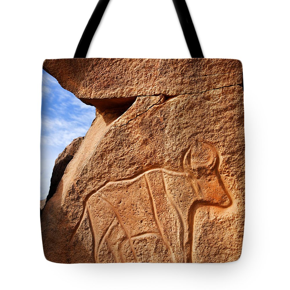 Libya Tote Bag featuring the photograph Ancient Engraving Of A Buffalo At The Wadi Matkhandouch In Libya by Robert Preston