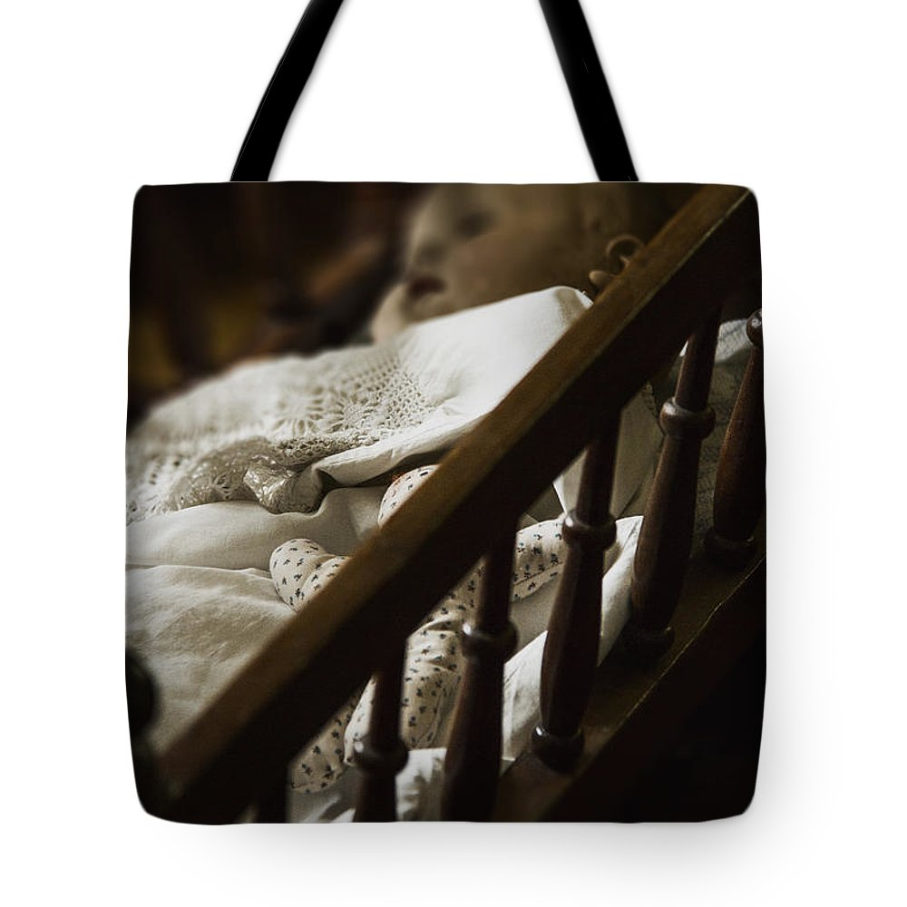 Old; Antique; Childhood; Doll; Eerie; Baby; Sleep; Sleeping; Heirloom; Nostalgia; Old; Retro; Toy; Vintage; Female; Male; Girl; Boy; Porcelain; Blanket; Bed; Crib; Play; Playing; Quilt; Dark; Darkness; Shadow; Shroud Tote Bag featuring the photograph Asleep In The Darkness by Margie Hurwich