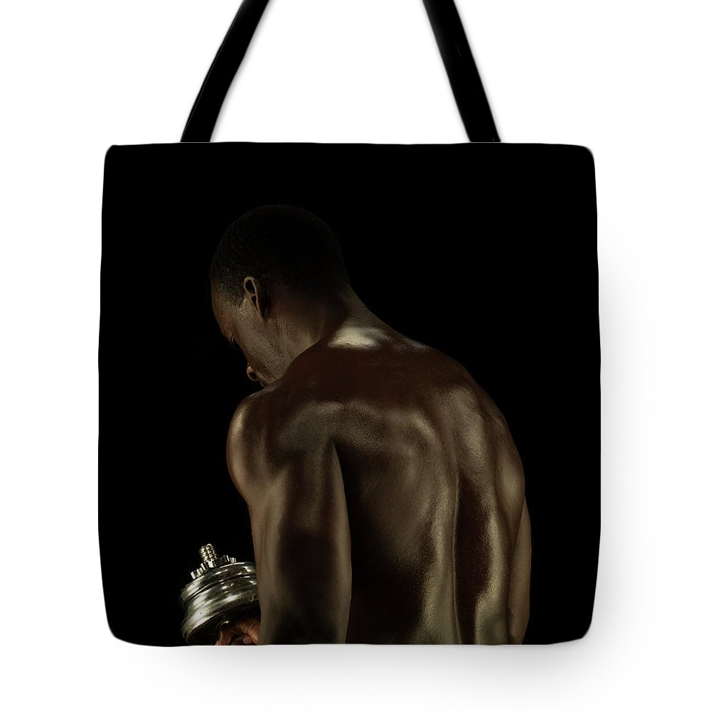 Mature Adult Tote Bag featuring the photograph Athletic Male Exercising With A Hand by Jonathan Knowles