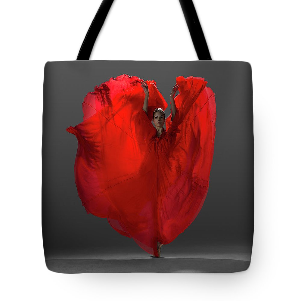 Ballet Dancer Tote Bag featuring the photograph Ballerina On Pointe With Red Dress by Nisian Hughes