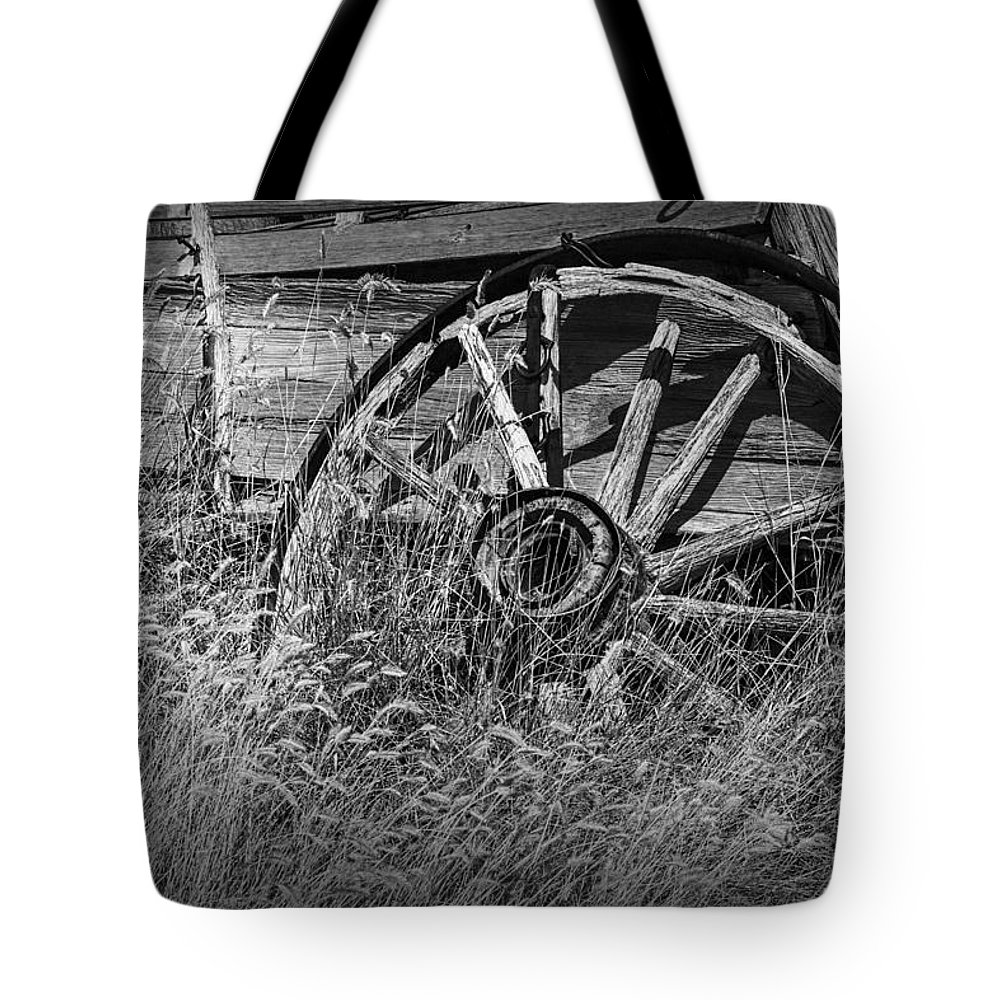 Art Tote Bag featuring the photograph Black And White Photo Of An Old Broken Wheel Of A Farm Wagon by Randall Nyhof