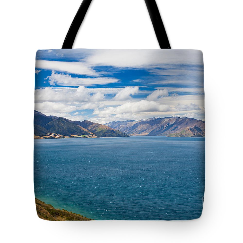South Island Tote Bag featuring the photograph Blue Surface Of Lake Hawea In Central Otago Of New Zealand by Stephan Pietzko