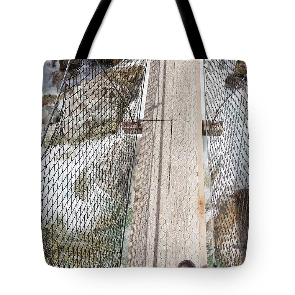 Activity Tote Bag featuring the photograph Boots On Narrow Swing Bridge Over White Water by Stephan Pietzko