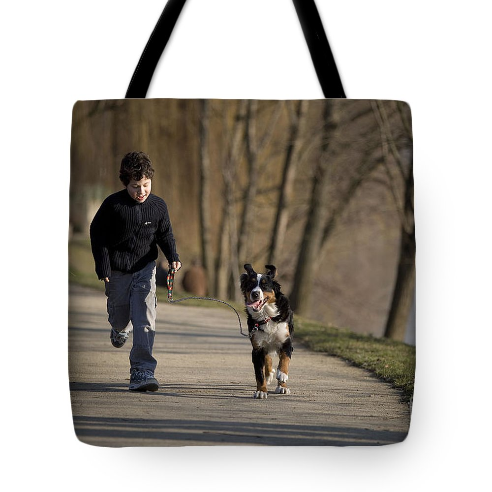 Bernese Mountain Dog Tote Bag featuring the photograph Boy Running With Dog by Jean-Michel Labat