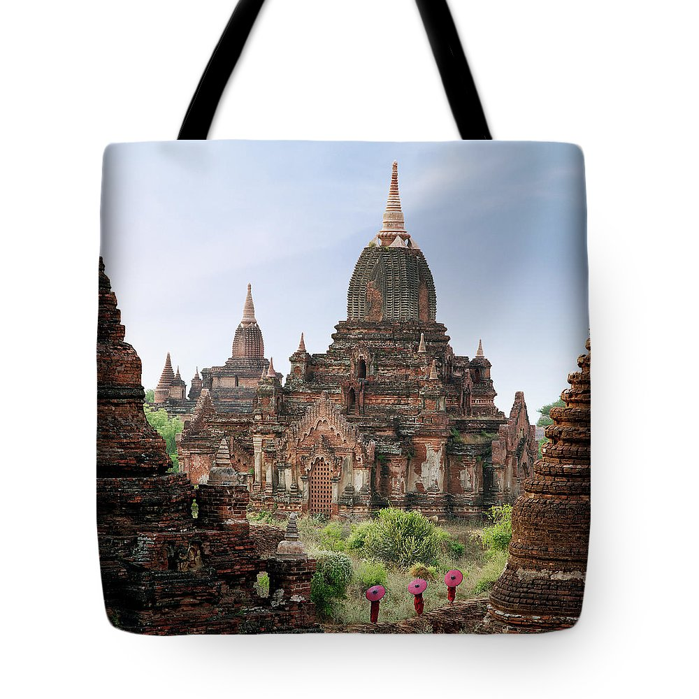 Tranquility Tote Bag featuring the photograph Buddhist Monks Walking Past Temple by Martin Puddy