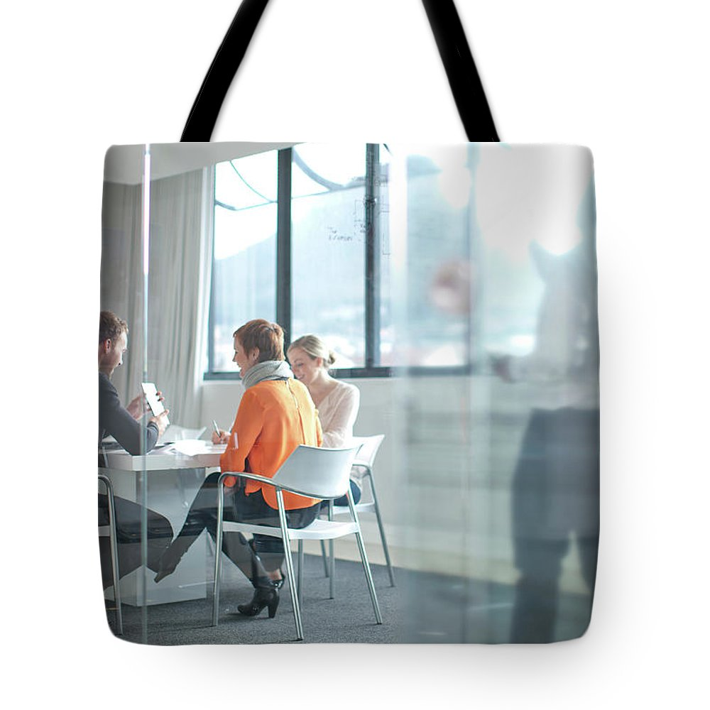 Young Men Tote Bag featuring the photograph Businesspeople Having Meeting At by Zero Creatives