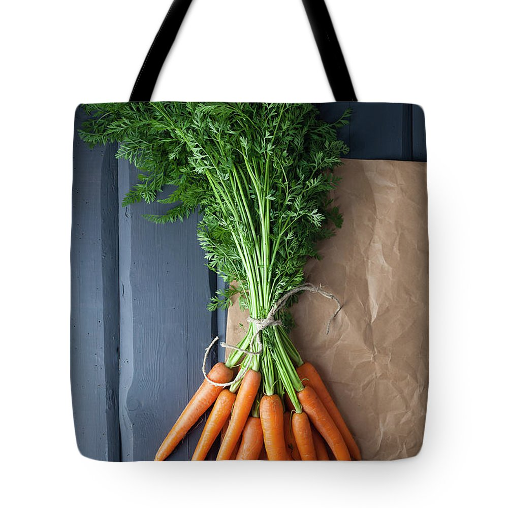 Bunch Tote Bag featuring the photograph Carrots With Brown Paper On Wooden by Westend61