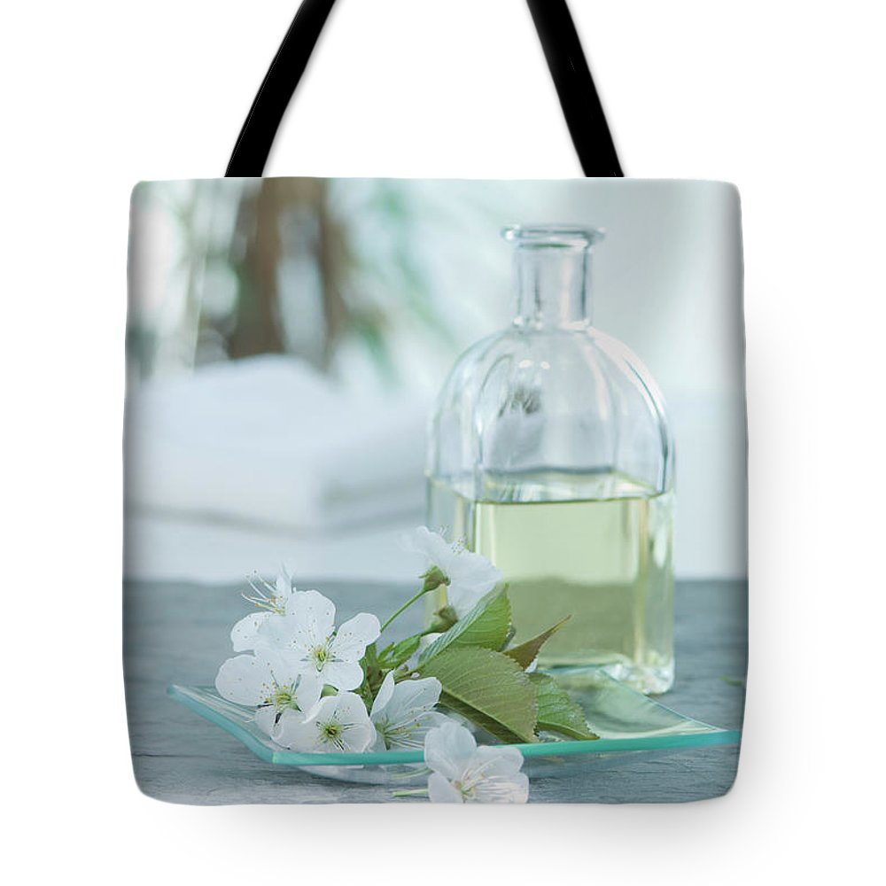 Spa Tote Bag featuring the photograph Cherry Blossom With Aroma Oil, Close Up by Westend61