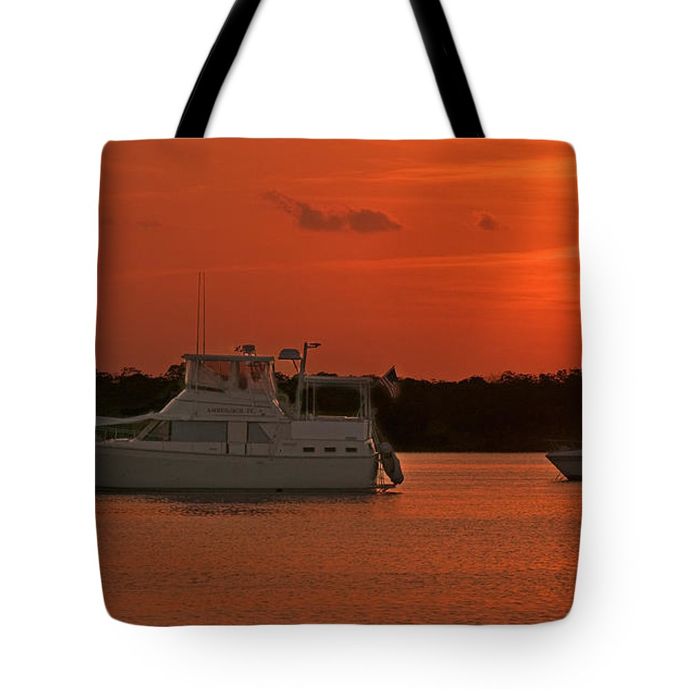 Coconut Palm Harbour In Keys Tote Bag featuring the photograph Cabin Cruiser And Red Sunset Over Harbour by Ginger Wakem