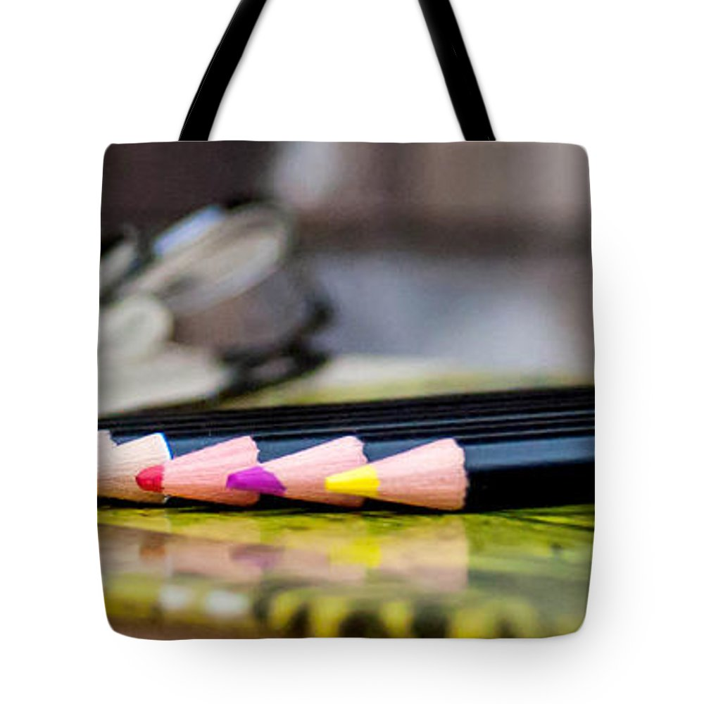 Colored Pencils On Book Tote Bag featuring the photograph Colored Pencils On Book by Mechala Matthews