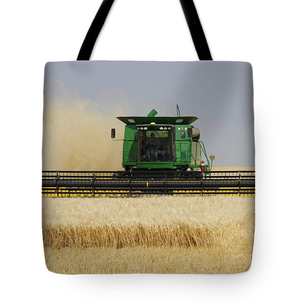 Light Tote Bag featuring the photograph Combine Working A Field On The by Peter Carroll