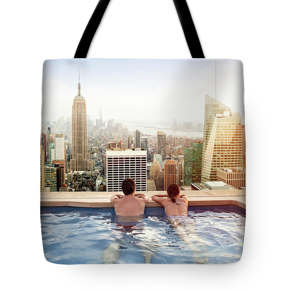 Recreational Pursuit Tote Bag featuring the photograph Couple Relaxing On Hotel Rooftop by Orbon Alija