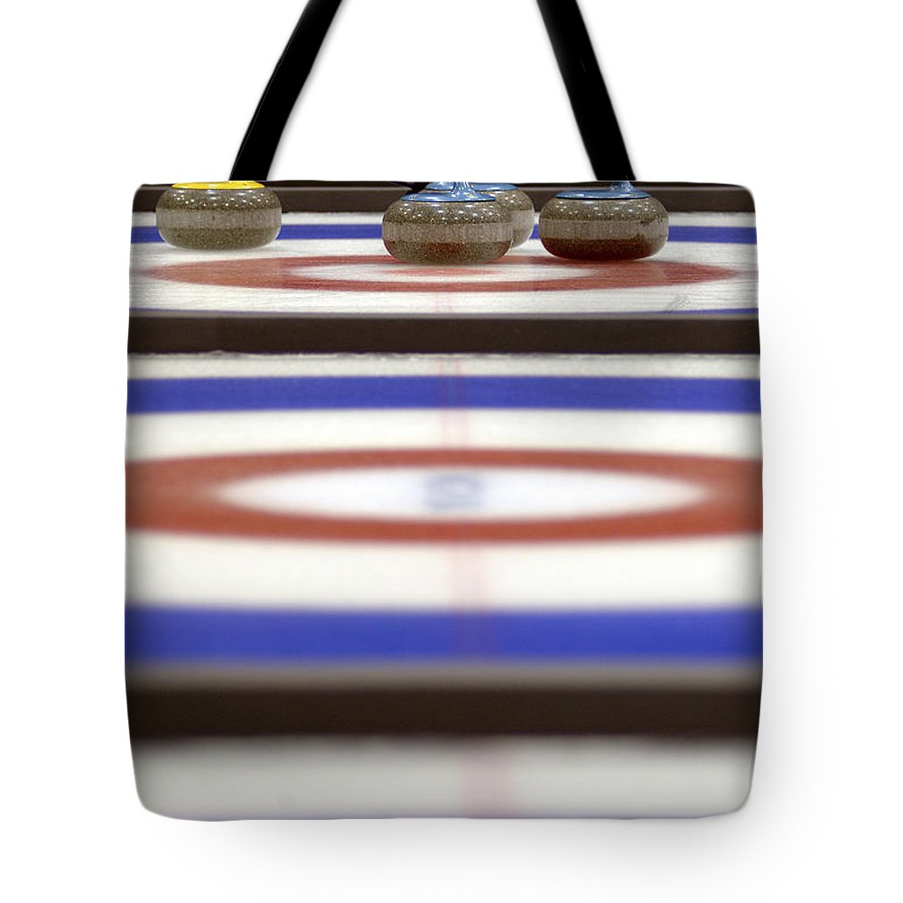 Light Tote Bag featuring the photograph Curling Rocks On Ice by Kevin Spreekmeester