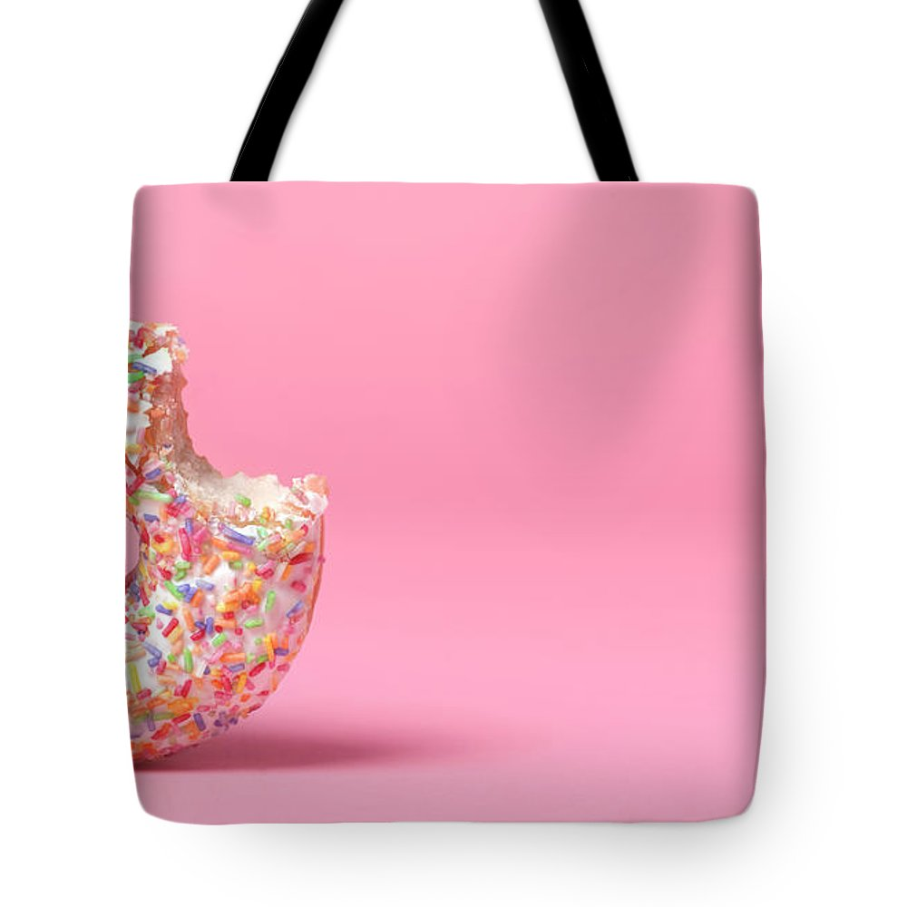 Unhealthy Eating Tote Bag featuring the photograph Doughnut On Pink With Bite Out by Peter Dazeley