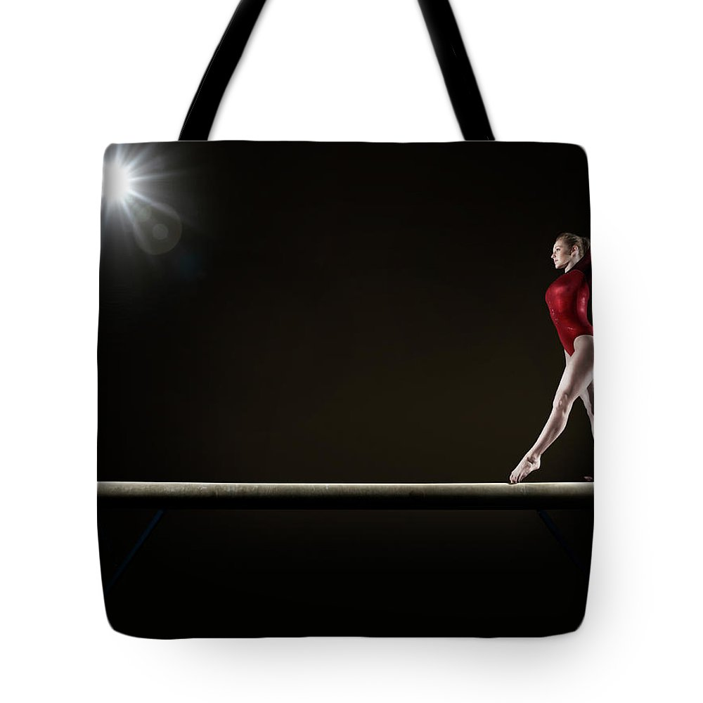 Human Arm Tote Bag featuring the photograph Female Gymnast Balancing On Beam by Mike Harrington