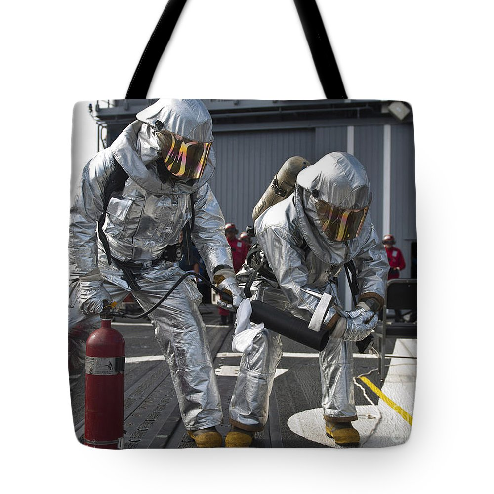 Us Navy Tote Bag featuring the photograph Firemen Confirm A Simulated Fire by Stocktrek Images