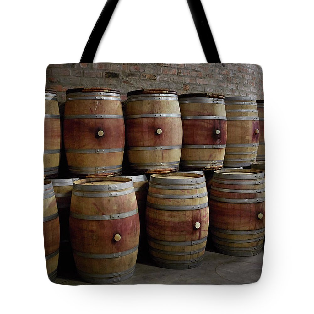 Stellenbosch Tote Bag featuring the photograph French Wine Barrels Stacked At Winery by Klaus Vedfelt