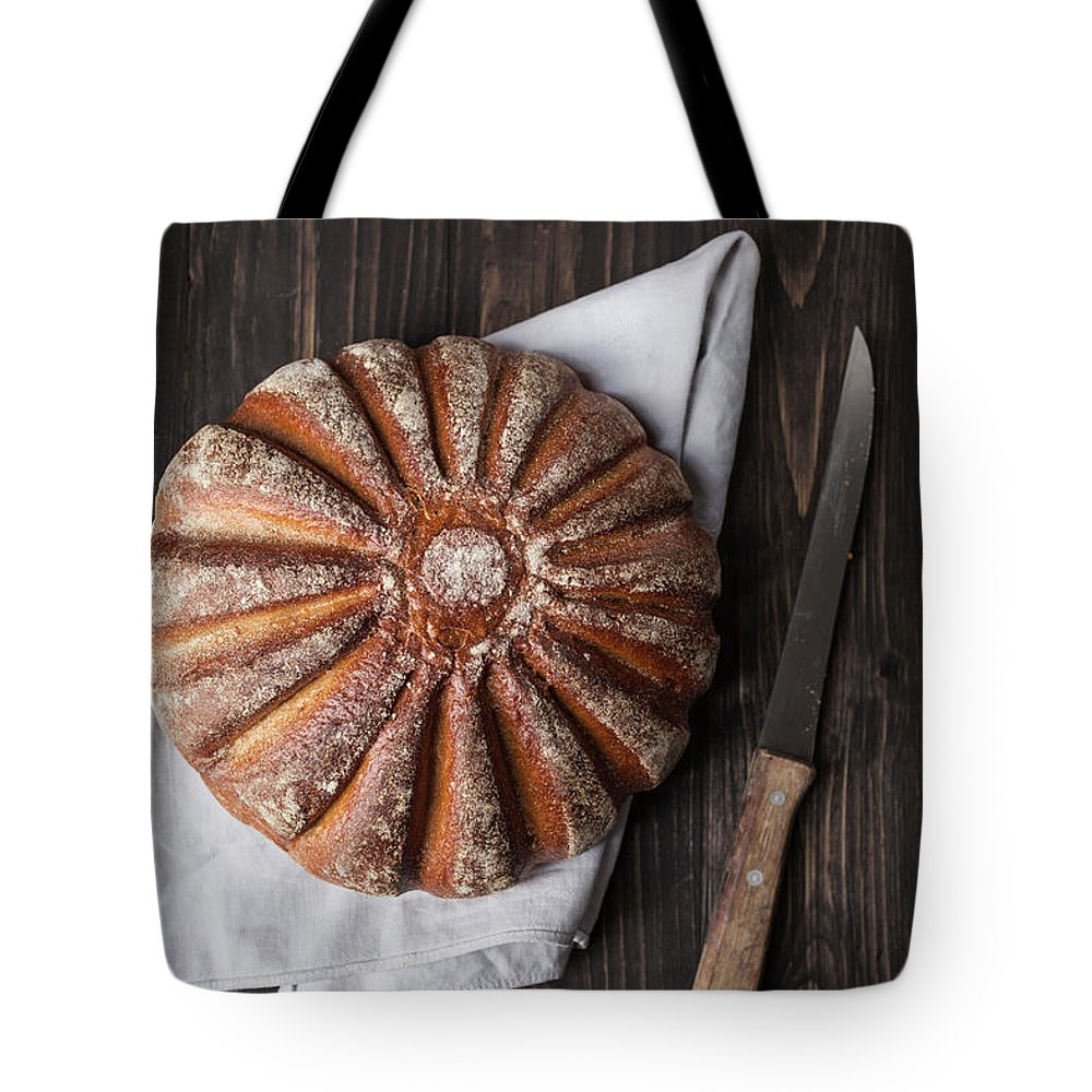 Kitchen Knife Tote Bag featuring the photograph Fresh Baked Bread With Kitchen Knife On by Westend61