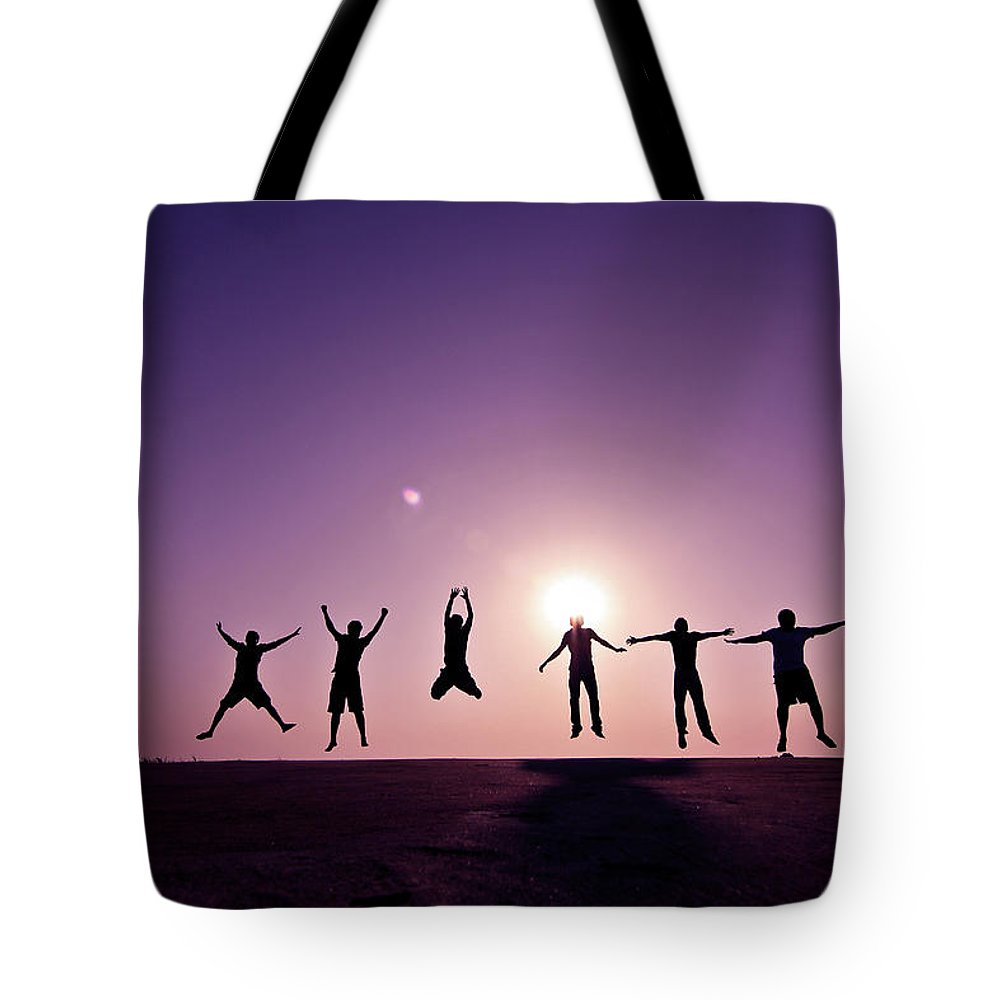 Human Arm Tote Bag featuring the photograph Friends Jumping Against Sunset by Kazi Sudipto Photography