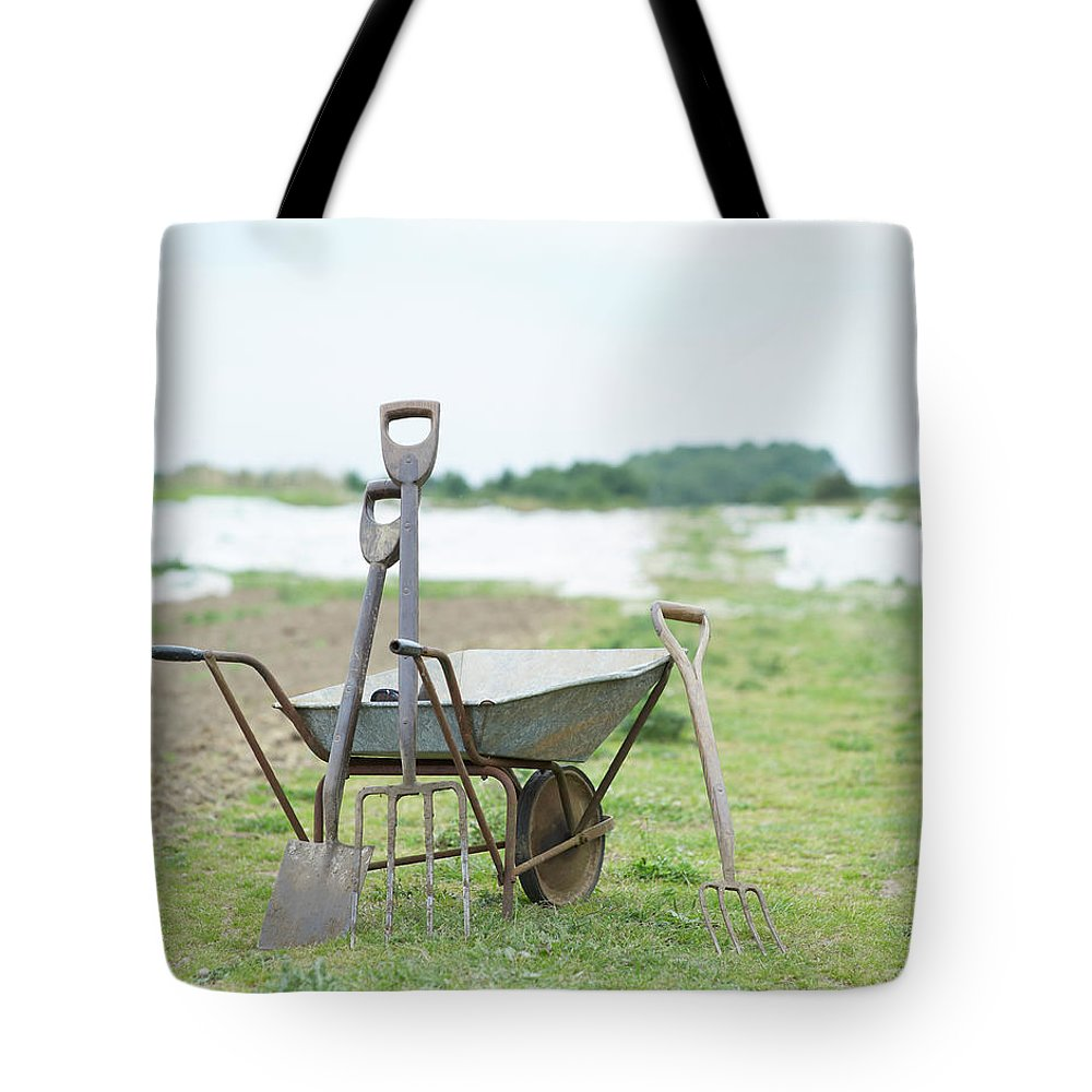 Grass Tote Bag featuring the photograph Gardening Tools And Wheel Barrow On by Dougal Waters