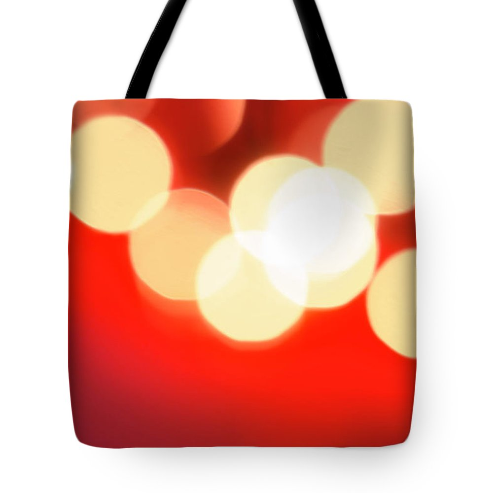 Christmas Lights Tote Bag featuring the photograph Glowing Light On Red Background, Studio by Tetra Images