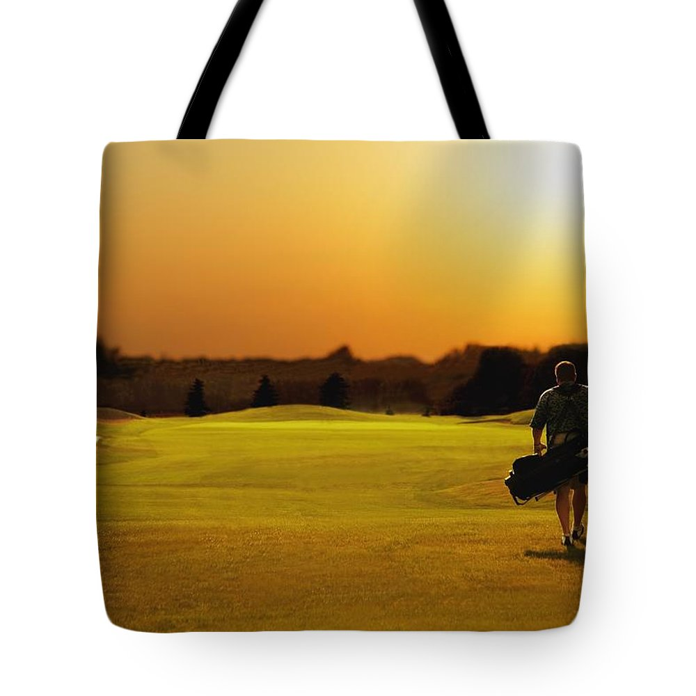Sunset Tote Bag featuring the photograph Golfer Walking On A Golf Course by Darren Greenwood