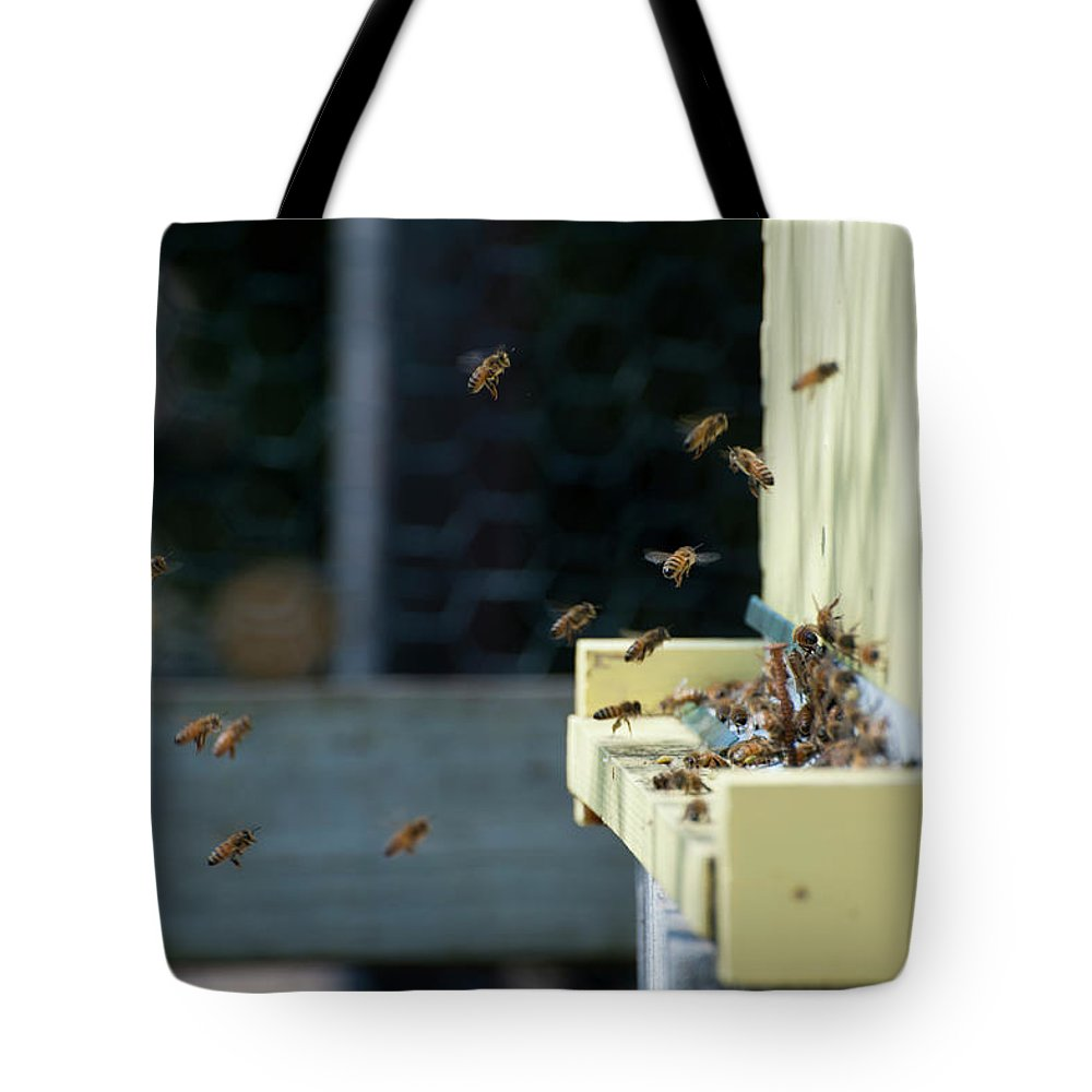 Animal Themes Tote Bag featuring the photograph Honey Bees Flying Around Hive Entrance by Monica Fecke