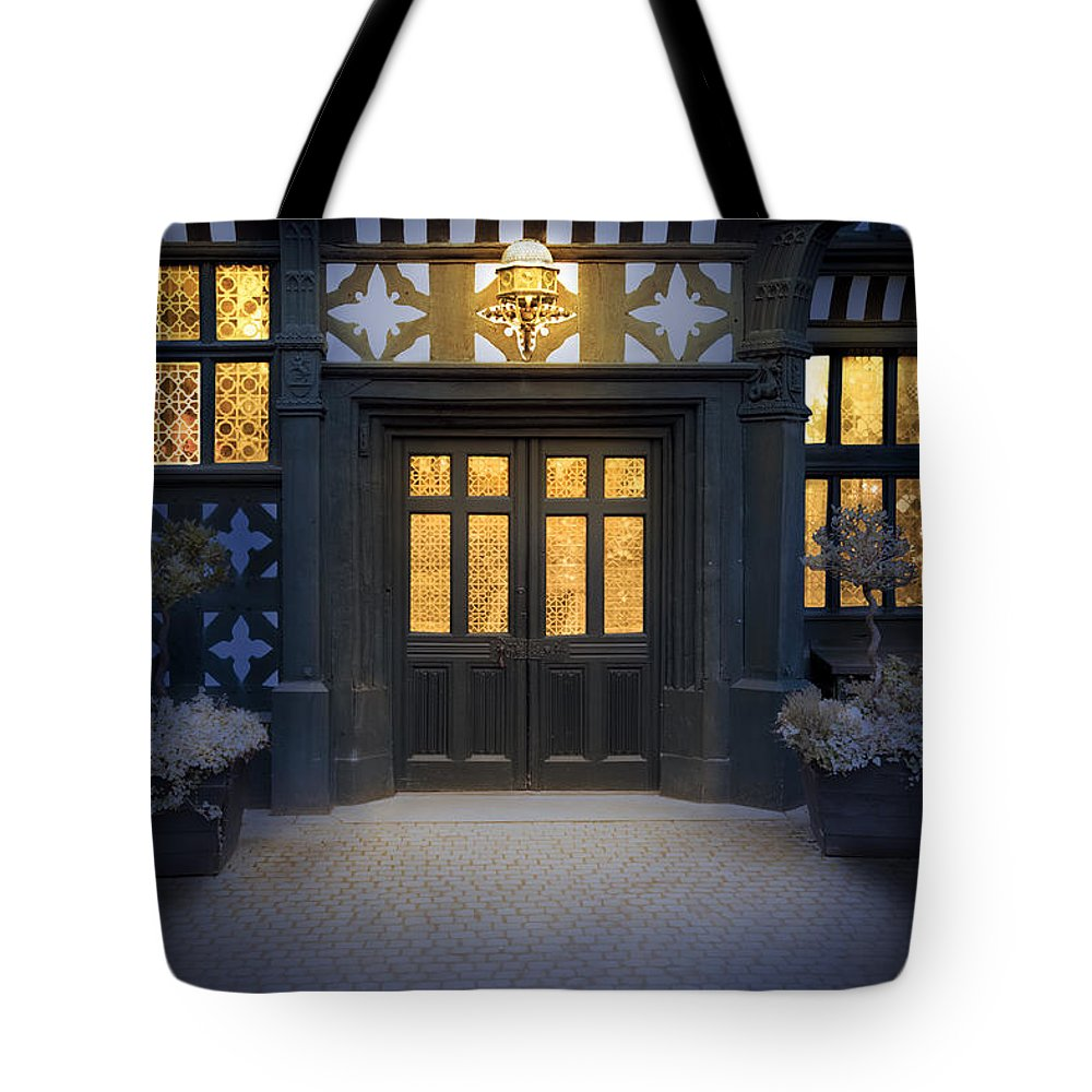 Tudor Tote Bag featuring the photograph Illuminated Doorway To A Timber Framed Tudor House Or Mansion At by Lee Avison