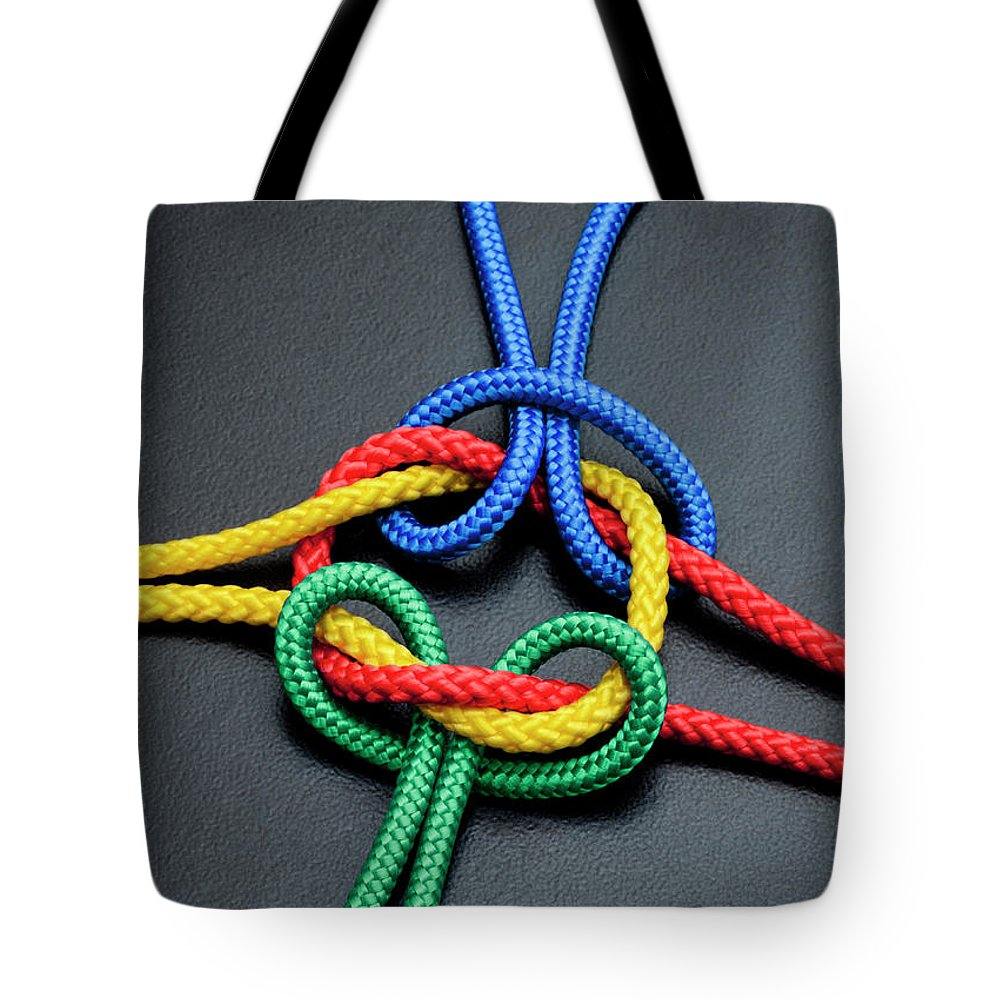 Teamwork Tote Bag featuring the photograph Intertwined Multicolored Ropes by Jorg Greuel