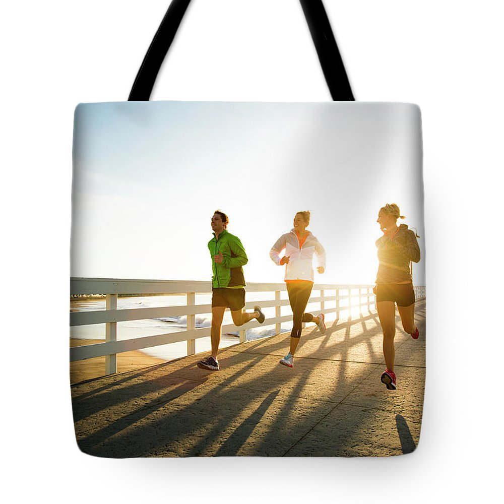 Young Men Tote Bag featuring the photograph Jogging Along The Coast by Jordan Siemens
