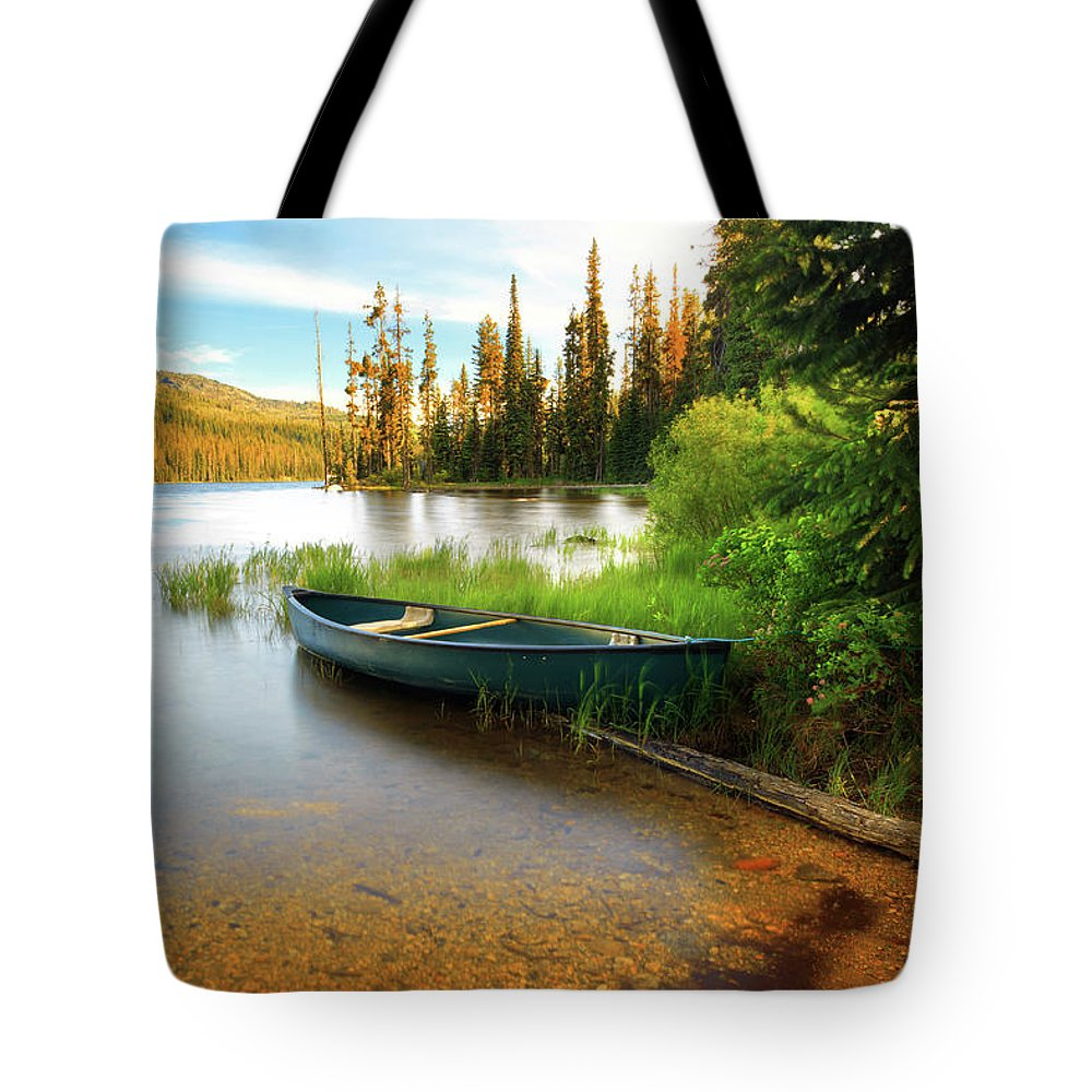 Tranquility Tote Bag featuring the photograph Lone Canoe On Shores Of Upper Payette by Anna Gorin