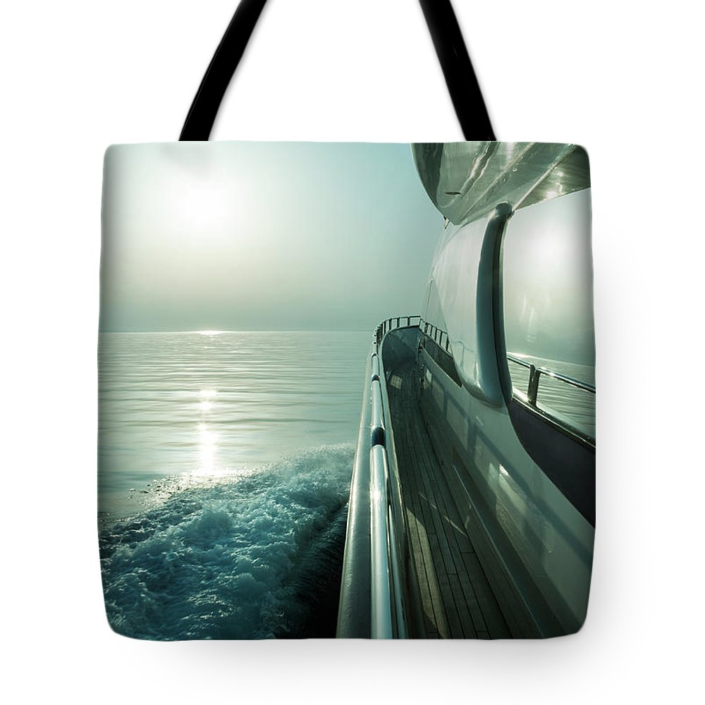 Desaturated Tote Bag featuring the photograph Luxury Motor Yacht Sailing At Sunset by Petreplesea