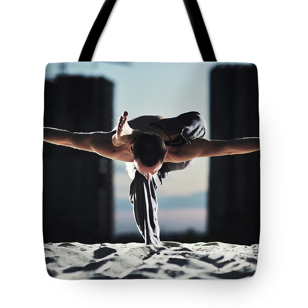 People Tote Bag featuring the photograph Man Holding Yoga Pose In The Sand by Myshkovsky