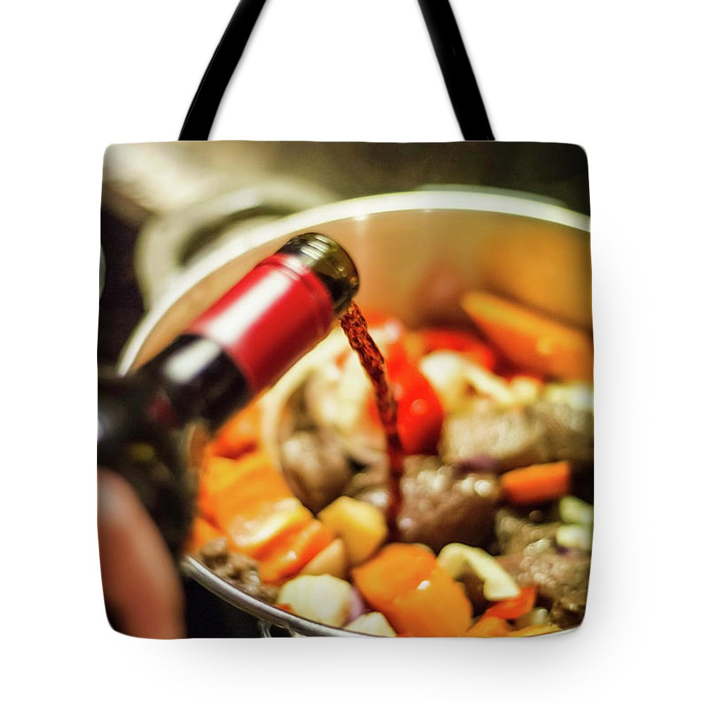 Mature Adult Tote Bag featuring the photograph Man Pouring Wine Into Vegetables by Manuel Sulzer