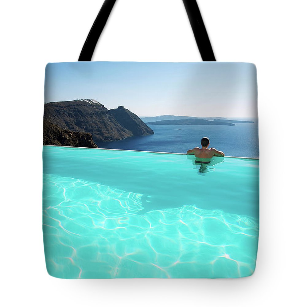 People Tote Bag featuring the photograph Man Relaxing Looking At Santorini by Peskymonkey